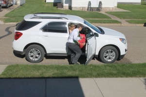 Alex helps tuck Paulina's dress into the car before they leave.