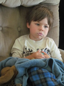 Jaxon watching tv with powdered donut on his mouth.