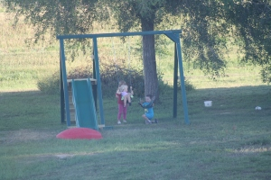 Jaxon with two girls on their swings.