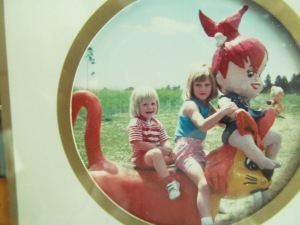 Victoria sitting with Jessica on a display at the Flintstone village in Custer, SD during a summer trip.