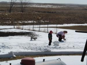 Jaxon and Paulina working on the snowman with Raja watching.