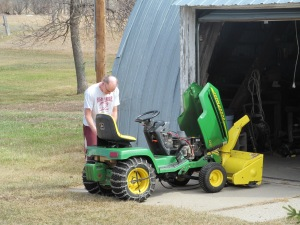 James changing the snow blower for the mower.