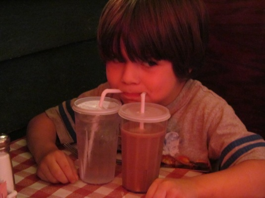 Jaxon drinking water and chocolate milk at the same time.
