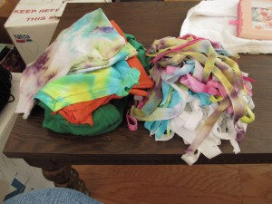 Piles of sleeves to be cut, and cut up strips to be sewed together into t-shirt yarns.