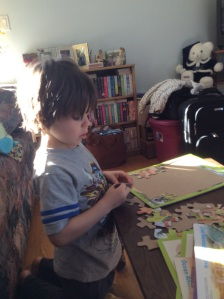 Jaxon setting puzzles. He was so particular about them that he did the pieces in order.