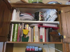 Cookbooks in the cupboard above the stove. See the junk on the top shelf.