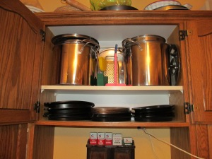 Large stock pots on top with a few odds and ends and the steak plates on the bottom so easy to reach.