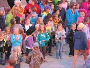 Jaxon in the crowd of children. He has on a yellow top, black hair just right of center.